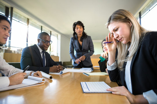Tired corporate executive worker shows signs of stress and fatigue at business meeting