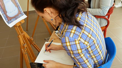 Female artist draws a pencil sketch drawing on canvas easel in art studio. Student girl learning to draw and paint.