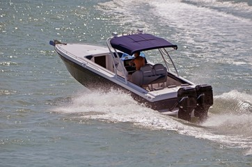 Motor boat powered by twin outboard engines cruising on biscayne bay,