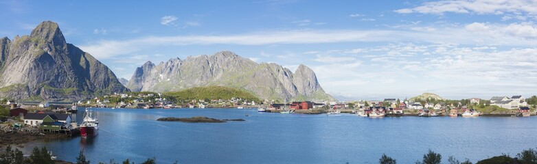 Panorama of the blue sea surrounding the fishing village and rocky peaks Reine Moskenes Lofoten Islands Norway Europe