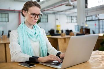 Female graphic designer using laptop at desk
