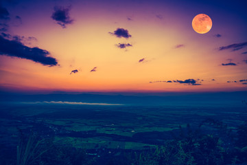 The full moon in the evening after sunset. Outdoors at nighttime. Vintage effect tone.