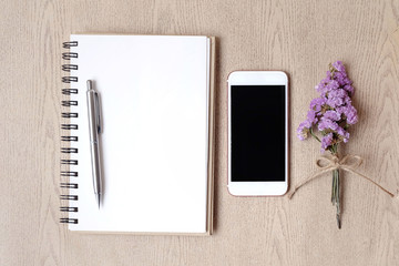 Mobile phone and notebook on wooden table and bouquet flower. Copy space .