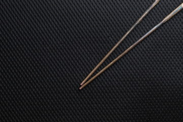 Chopsticks put on dark background scene.