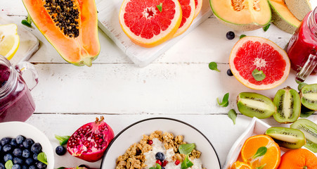Different fruits on white wooden table. Healthy food concept.