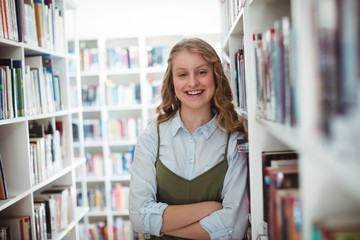 Portrait of schoolgirl standing with arms crossed in library