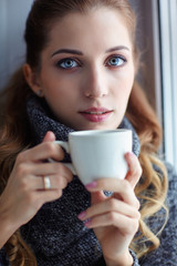 Young pretty woman in wool sweater with white coffee cup in hands