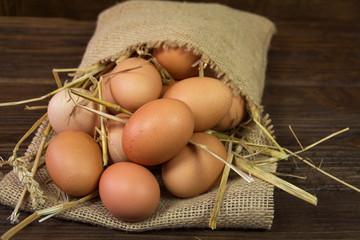 Chicken eggs in bag on wooden background