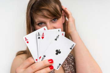 Beautiful girl hides behind poker cards