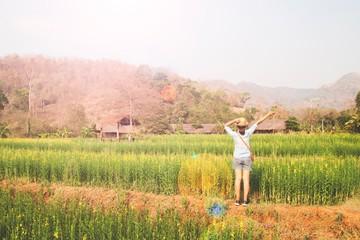 Happy girl traveler standing in flowers field, Summer vacation