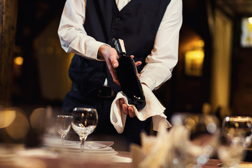The waiter offers visitors wine,Waiter in uniform waiting an order,Waiter with a white towel on his hand,Confident waiter,A pub.Restaurant.Classic.Evening.European restaurant