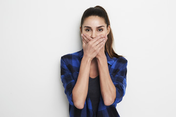 Woman with hands over mouth in studio