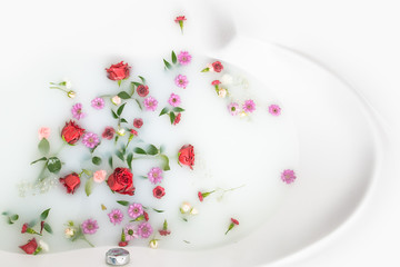 mix flower petals and leaves in milk bath, background or texture for massage and spa, relax