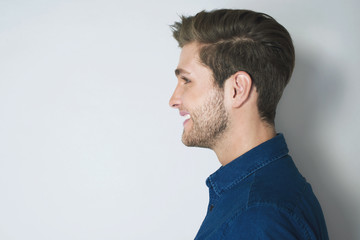 Handsome profile portrait of young smiled man. Attractive man side look isolated on grey background