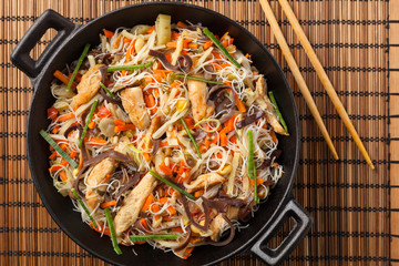 Rice noodles with chicken, mushrooms mun and vegetables in wook.