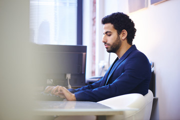 Arab businessmanin a jacket sitting in the workplace, typing on a keyboard in the office
