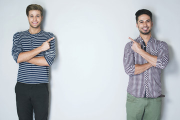 Look over there. A photo of two young handsome men, smiling and cheerfully pointing at the wall between them, dressed in casual clothes against light grey background. Selective focus
