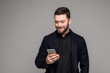 Happy man in black suit typing sms on smartphone