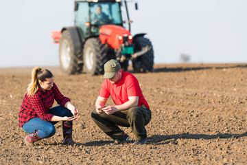 Young farmers examing  dirt while tractor is plowing fields