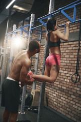 Personal trainer helping woman with pull ups.