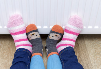 Woman and child wearing colorful pair of striped woolly socks warming cold feet in front of heater