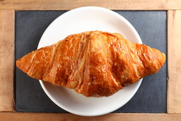 The fresh croissant put on the white dish represent the pastry and food concept related idea.