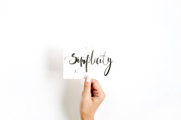 Minimal pale composition with girl's hand holding card with word Simplicity written in calligraphic style on paper on white background. Flat lay, top view