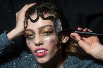 Pretty fashion girl putting holiday glitter makeup