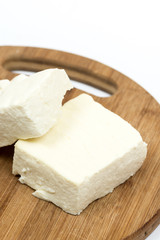 Slices of white feta cheese on the wooden board