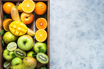Green yellow and orange fruits in wooden tray. Top view organic food background