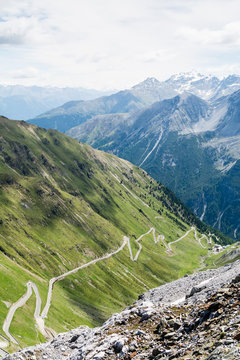 Alp road surrounded by blue alp high mountains and green hills. Steep descent of Passo dello Stelvio in Stelvio Natural Park, Tyrol, Italy.