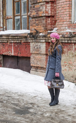 Girl in a pink beret and a gray-blue coat standing in the yard of the old house / The picture was taken in Russia, in the city of Orenburg, in a courtyard on Kobozev Street