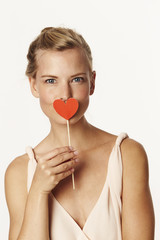Woman holding heart shape over mouth, portrait