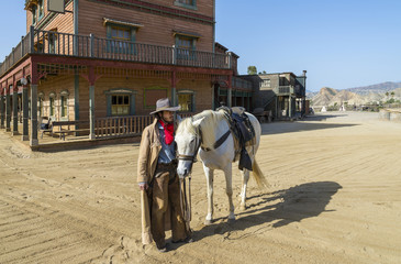 Wall Mural - Cowboy with his horse at the Western Town at Mini Hollywood, Tabernas, Almeria Province, Andalusia, Spain
