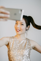 young asian woman taking a selfie with smartphone