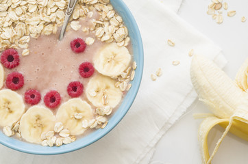Smoothies in a plate with oatmeal, banana and raspberries