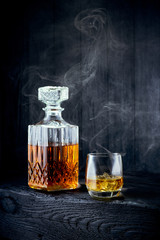 Glass of whiskey and carafe on a black wooden table