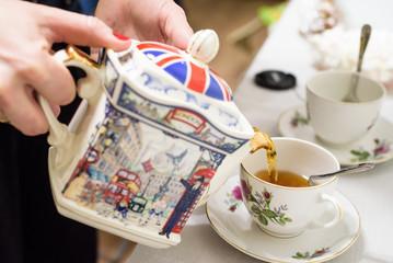 Tea poured into tea cup with British symbols Fototapete