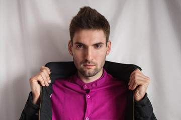 Young attractive cheerful man with dark hair with a beard in a purple shirt and a black jacket on a white background. Men's style. Male portrait. Studio photography