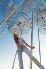 Girl holding an umbrella. Installation Flying umbrellas, Greece. Group of umbrellas on blue sky background. Concept of summer travel. Umbrellas in Thessaloniki, Greece.