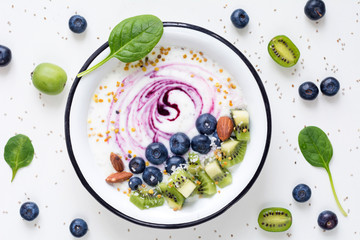 Smoothie bowl with acai berry, kiwi, blueberries, almonds, coconut, bee pollen and baby spinach on white background. Top view of healthy detox smoothy bowl