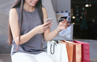 Woman hands holding credit card and shopping online through smartphone while sitting beside shopping bag in the department store