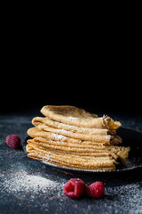 Vegan pancakes, russian pancakes or crepes on black plate. Selective focus, copy space