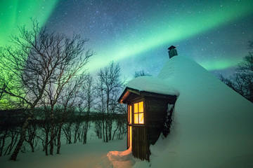 Northern lights over snowcapped cabin