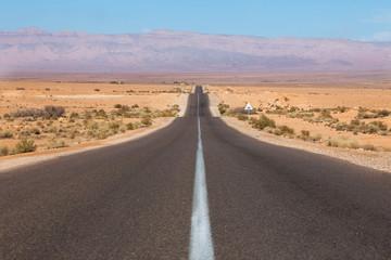 route droite au milieu d'un désert de sable