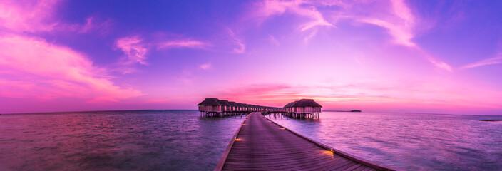 Fototapeta Sunset on Maldives island, water villas resort. Beautiful sky and clouds. Beautiful beach background for summer travel with sun, beach wooden jetty. Summer mood sun beach background concept.