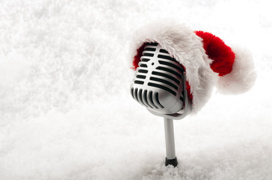 Carols and Christmas music concept with a microphone wearing a santa hat isolated on white snow with copy space