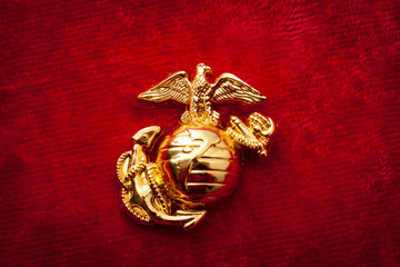 Macro image of the US Marine Corps emblem on red velvet as background and a grungy aesthetic. Semper fidelis or Semper Fi is Latin for - always faithful - is the motto of the United States Marines