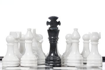 Black king and white chessmen on chessboard