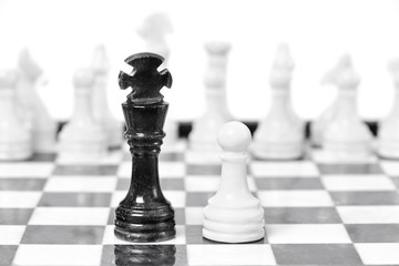 Black king and white  pawn on chessboard
